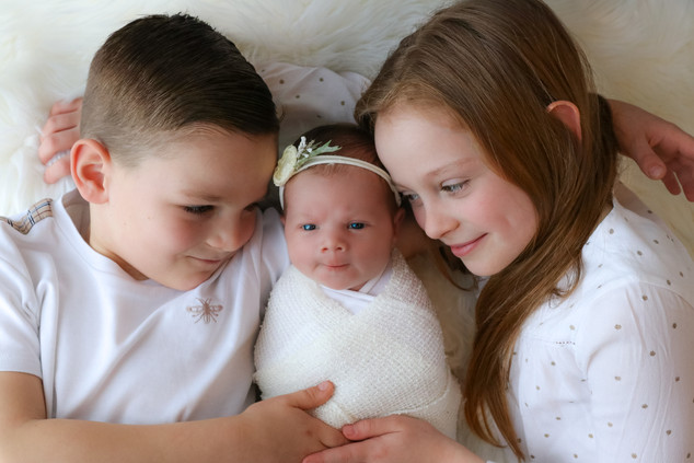 two older children laying down on a white rug together with a newborn baby girl in the middle, all wearing white