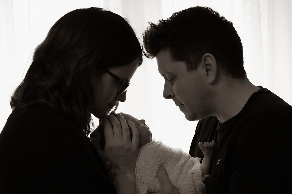 silhouetted family shot of woman man and newborn