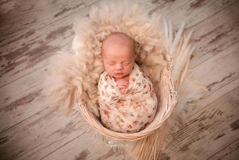beautiful sleeping baby girl wearing a cream and brown wrap
