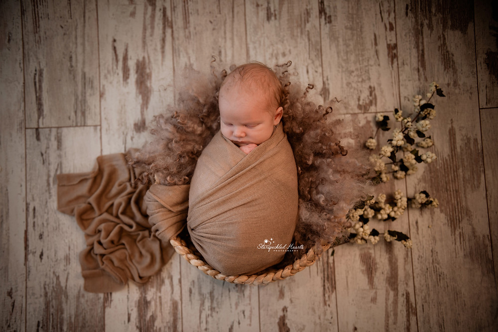 sleeping newborn baby boy wrapped in a brown swaddle lying in a basket surrounded by snowberries