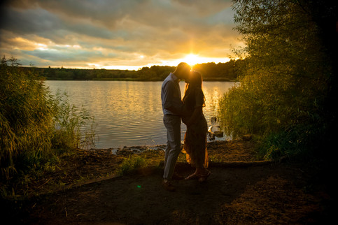 man and woman kissing standing in front of a large lake with the sun setting behind them