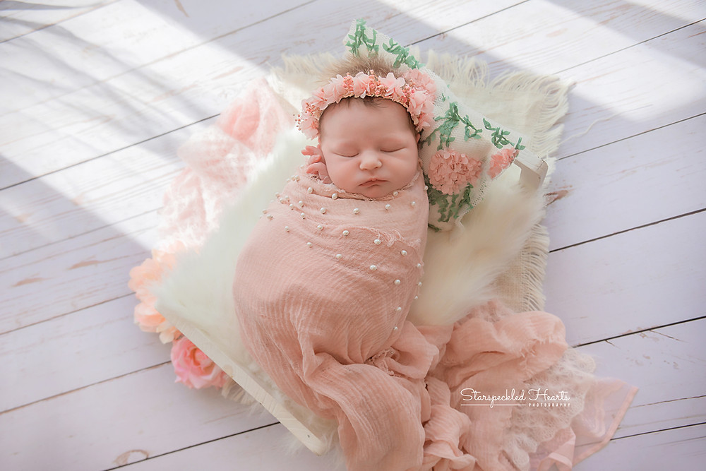 newborn baby wrapped up in a pink pearl embellished wrap, lying on a little white wooden bed with a little pillow for her newborn photoshoot in farnham, surrey