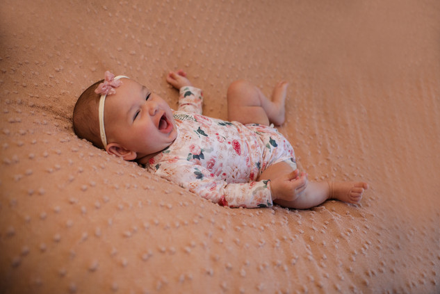 smiling baby girl wearing a pink floral romper, laying on a pink textured blanket
