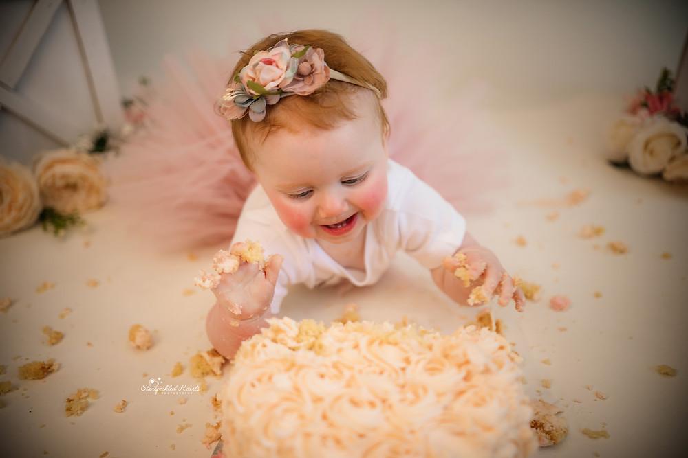 close up of a baby girl eating cake. cake smash photographer near me hampshire surrey