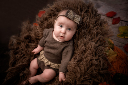 autumnal newborn studio photo of baby girl with eyes wide open wearing a brown romper with a lace trim