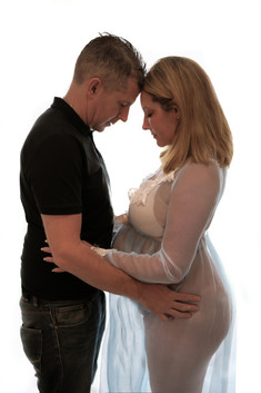 full body shot of pregnant woman wearing a white lacey sheer maternity gown and a her husband, embracing