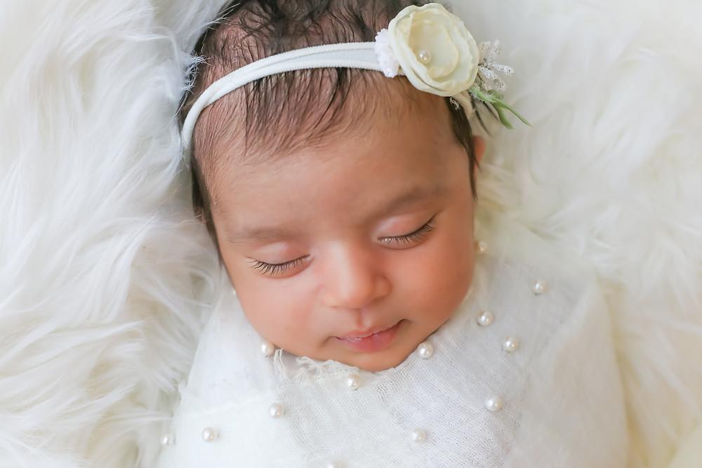 gorgeous sleeping newborn girl with long eyelashes dressed in white