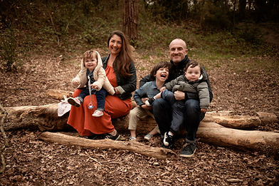 a family of 5 sitting on a large log outdoors, all with big smiles for their outdoor family session with starspeckledhearts photography