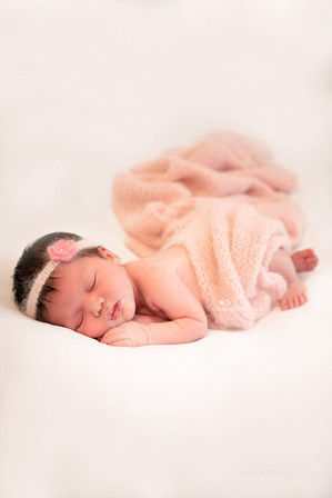 beautiful sleeping baby girl with a pink blanket wrapped loosely around her