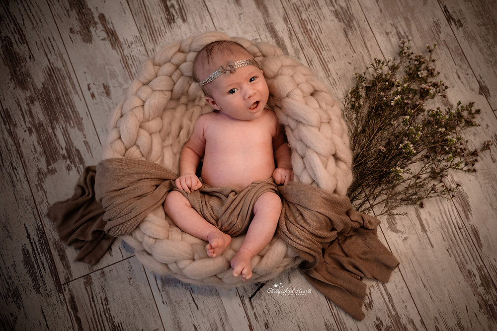 newborn baby girl lying in a woven basket surrounded by waxflowers, wearing a sparkly headband and a matching brown wrap draped over her for her newborn photography session in Aldershot, Hampshire