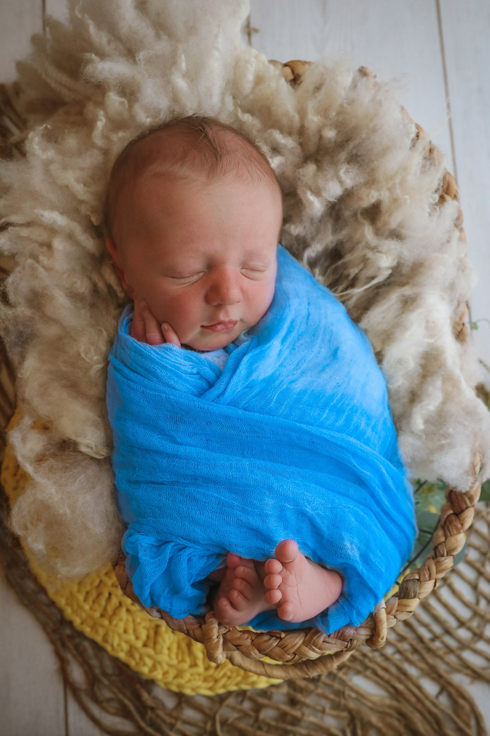 sleeping newborn wrapped in bright blue laying in basket