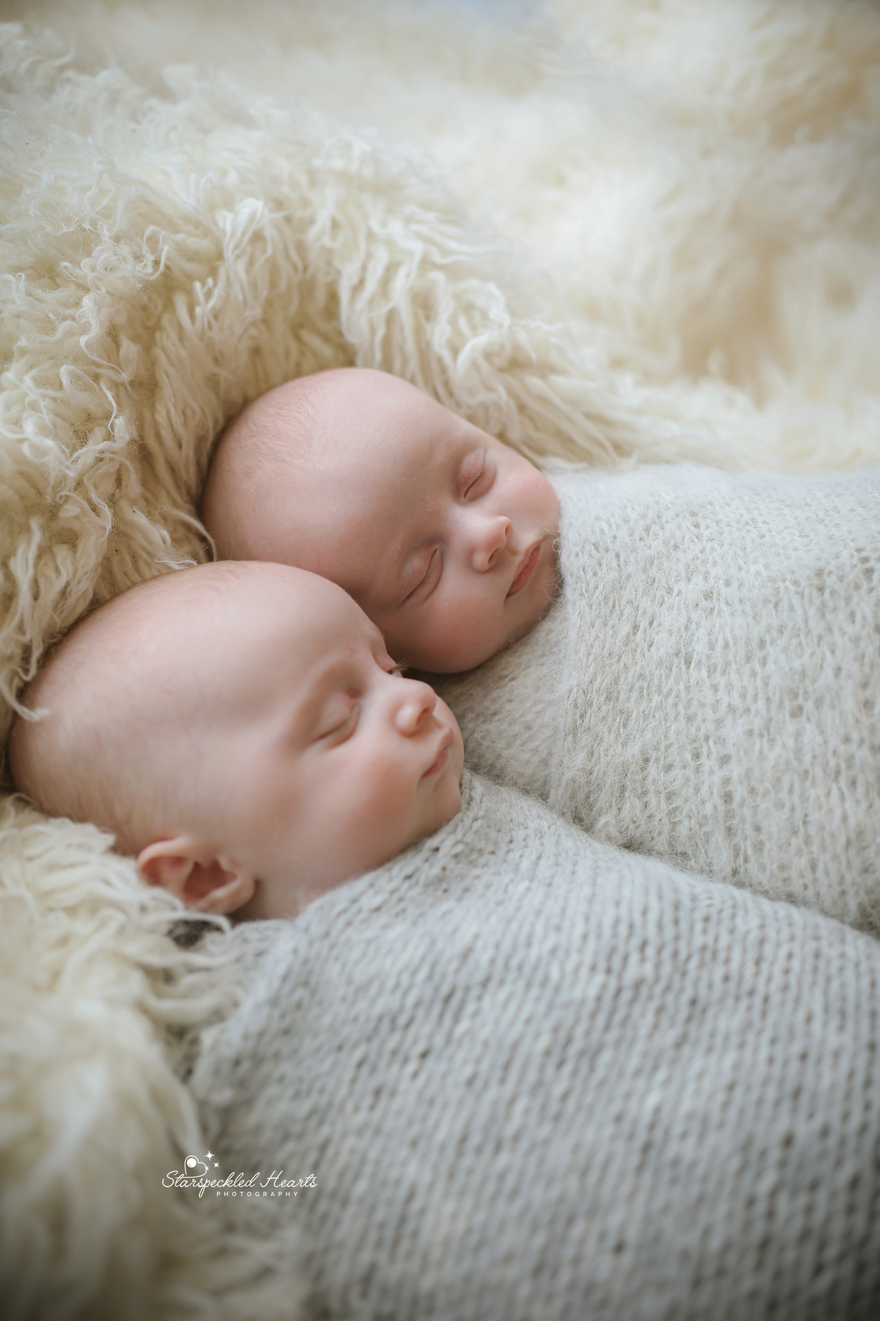 gorgeous identical twin boys fast asleep, wrapped in grey and laying cuddled up together on a white rug