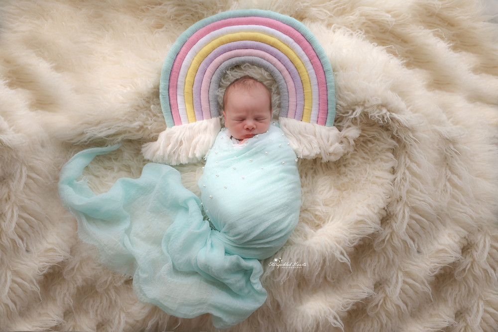 gorgeous sleeping baby girl wrapped in baby blue with a macrame rainbow over her head