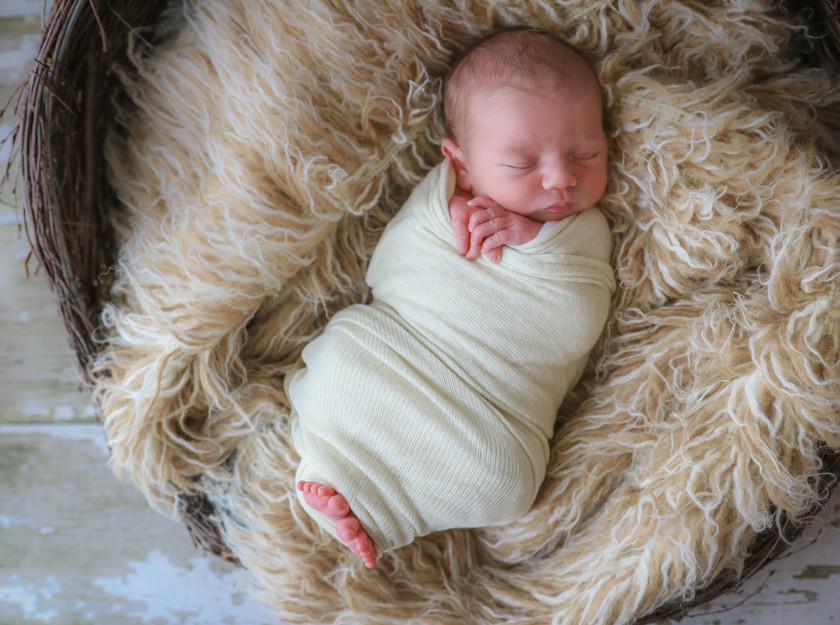 sleeping newborn baby wrapped lying on furry rug