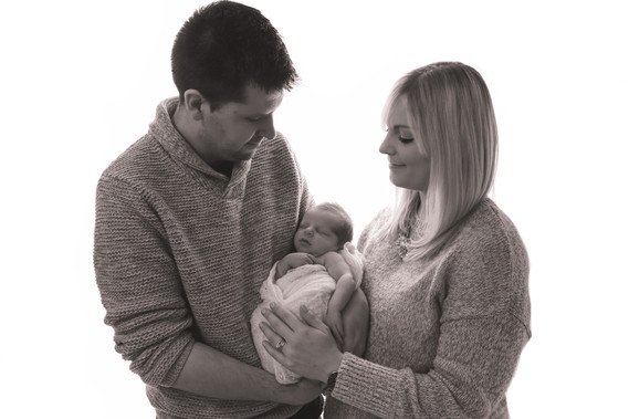 a man and woman wearing all grey holding a swaddled newborn in their arms, both gazing lovingly down at their baby, in black and white