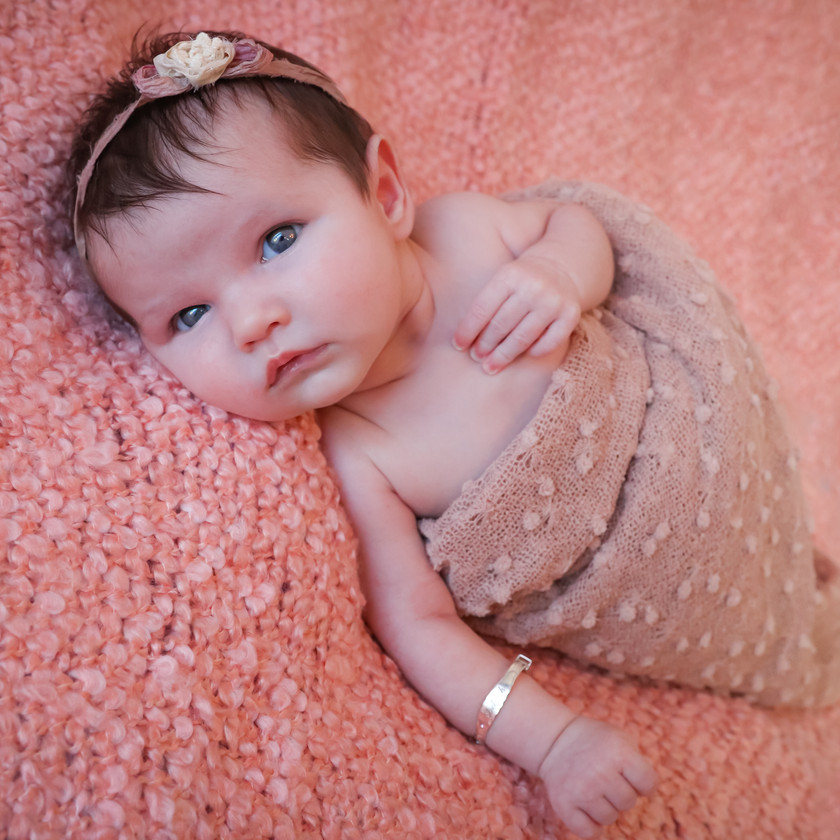 blue eyed newborn on a pink textured rug wrapped in pink