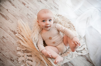 little boy with big blue eyes lying in a basket with a big smile on his face for his baby photoshoot with starspeckled hearts photography
