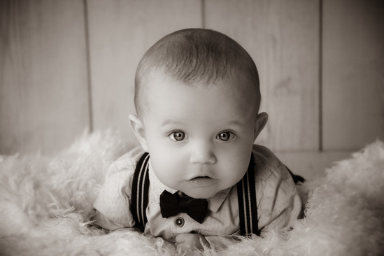 gorgeous baby boy laying on his tummy, propped up on his elbows wearing braces and bow tie