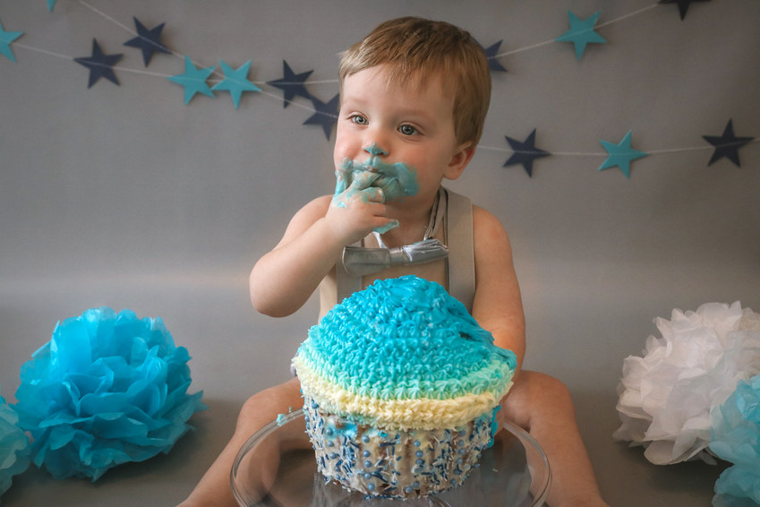 little boy licking blue icing off his finger