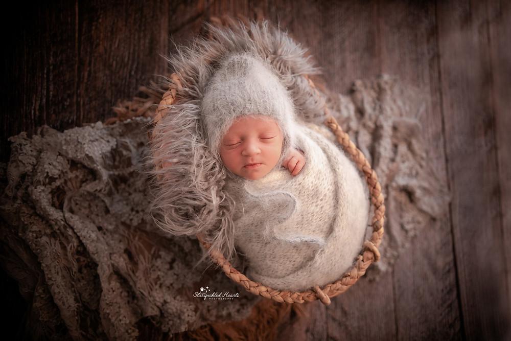 sleepy newborn girl wearing a grey knitted bonnet and wrap set, lying in a basket with wicker trim on a dark wooden floor