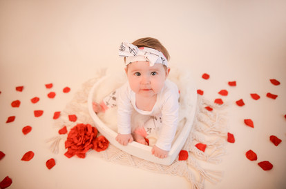 sweet baby girl wearing a white outfit with matching headbands, sat in a white heart bowl surrounded by rose petals for her valentines day session with starspeckled hearts photography