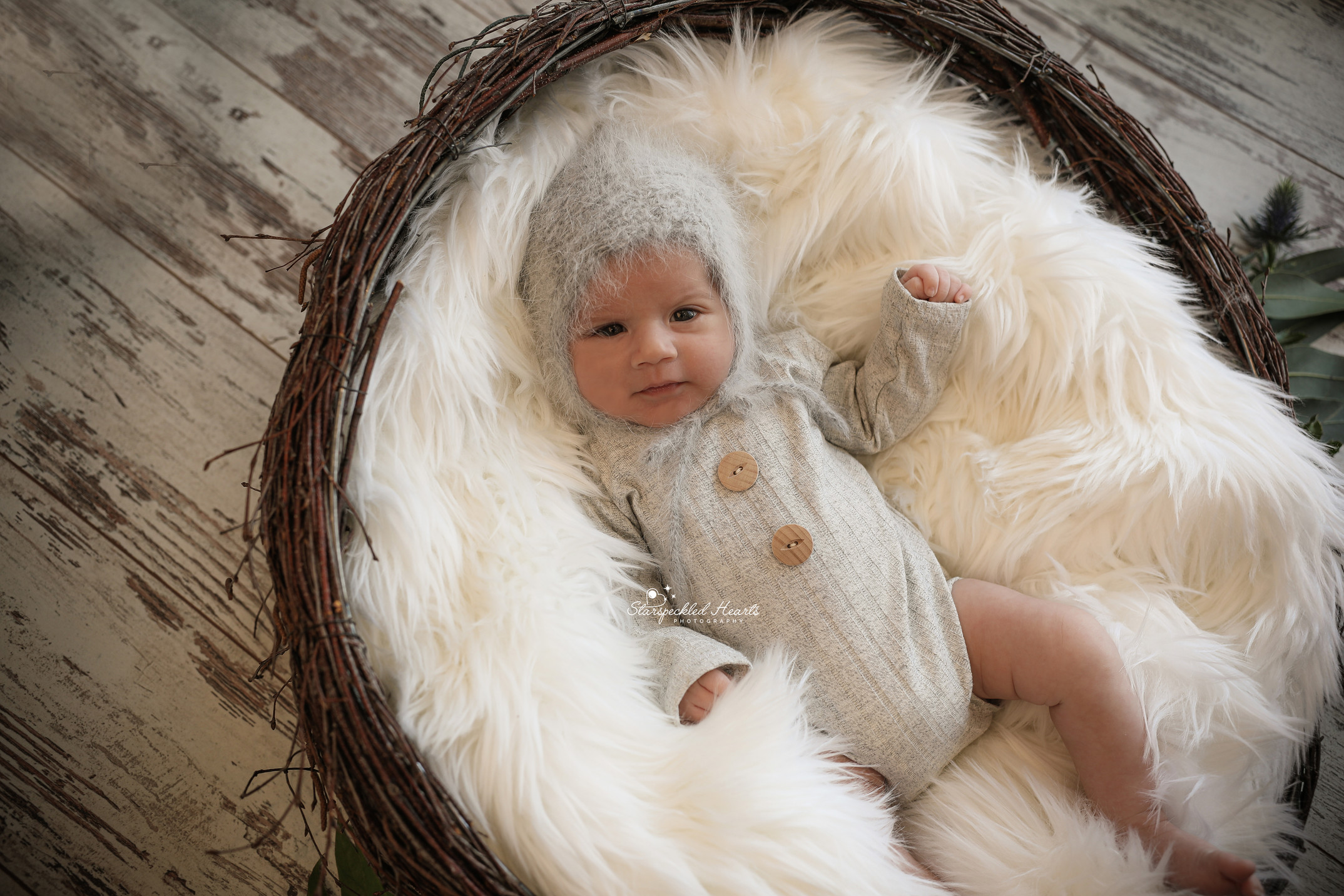 baby boy lying on a white fluffy rug in a wicker basket, wearing a grey romper and grey hat