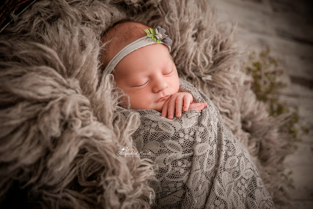 sleeping newborn with her hands folded under her chin, wearing a grey lace wrap and matching headband for her newborn photography session in surrey hampshire aldershot