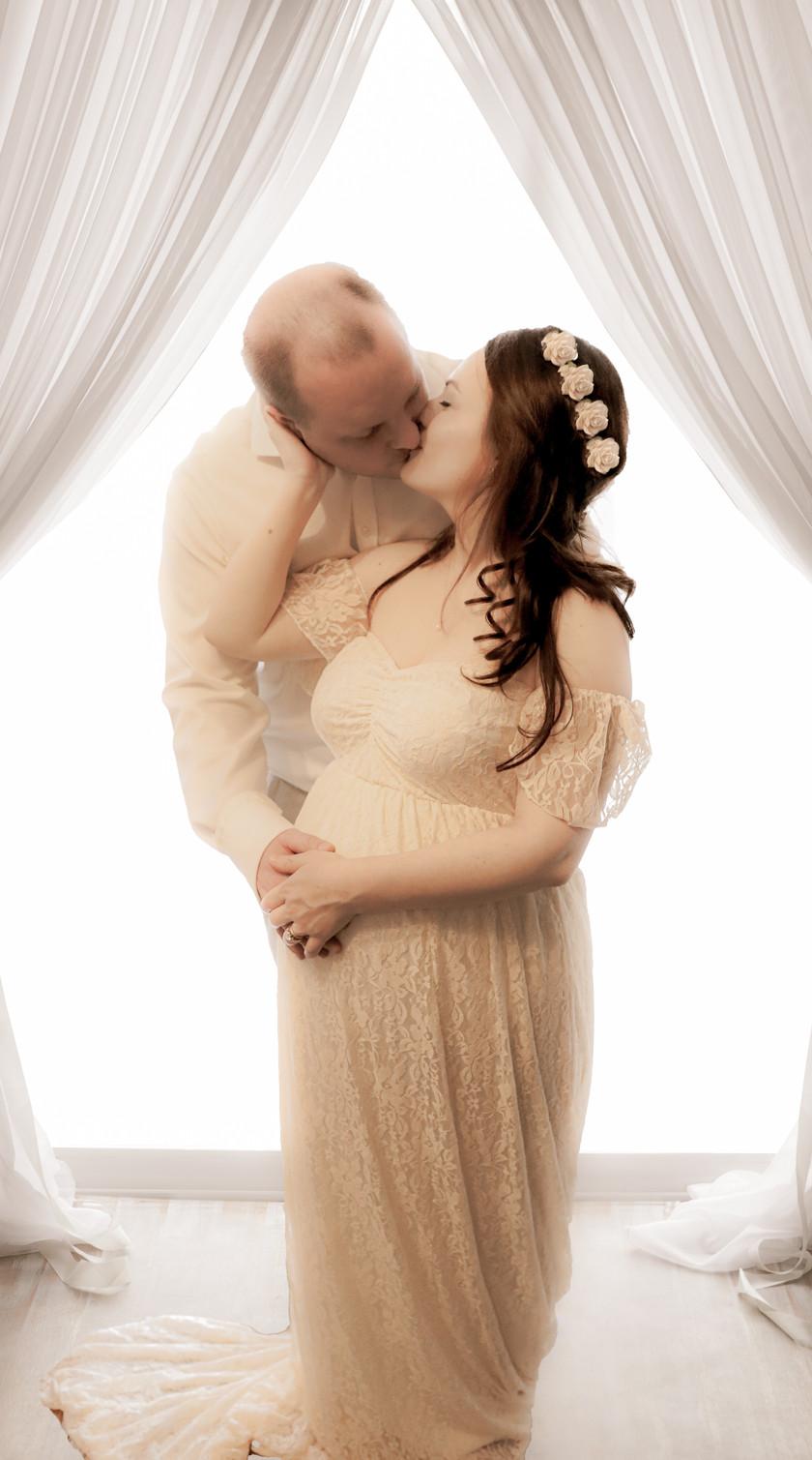man and pregnant woman kissing