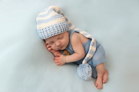 newborn baby boy fast asleep wearing a blue knitted romper and blue and white striped hat