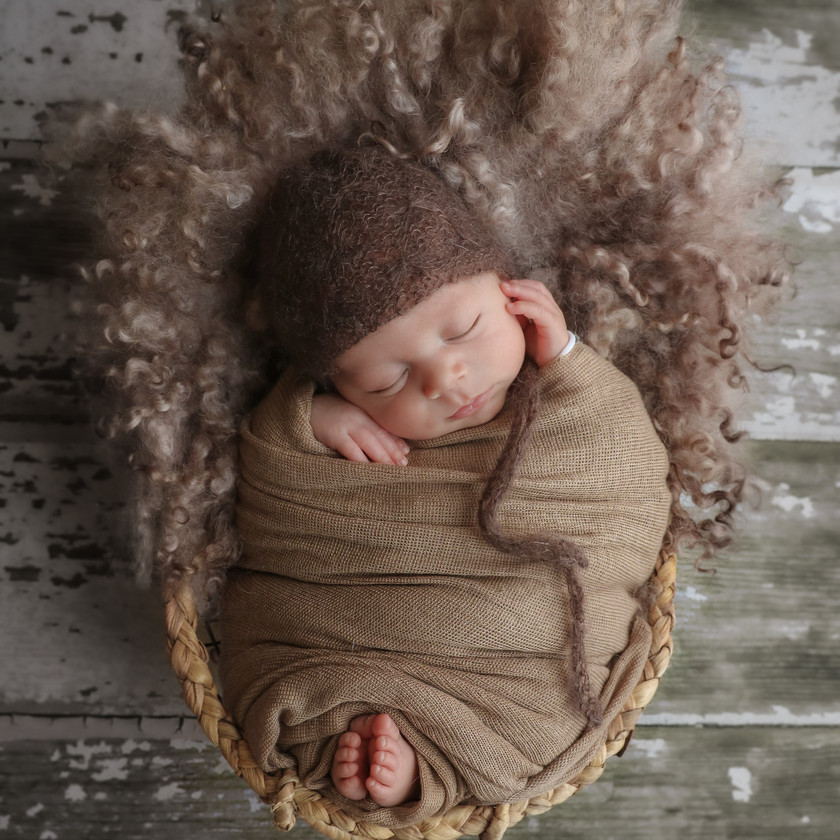 gorgeous sleeping baby boy wearing a brown knitted bonnet and brown wrap