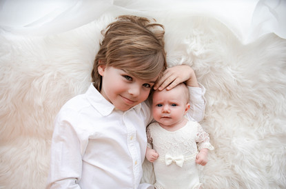 adorable brother and little sister both dressed in white, laying next to each other on a white fluffy rug for their baby session with starspeckled hearts photography