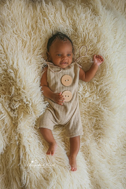 gorgeous baby boy wearing a brown romper, lying on a white fluffy rug