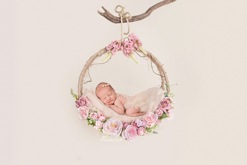 newborn lying in a pink floral hoop for her newborn session in aldershot hampshire
