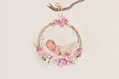 adorable baby girl lying in a flower wreath held up by a branch for her newborn session by starspeckled hearts photography in aldershot