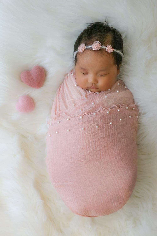 sleeping newborn girl in pink laying on white rug