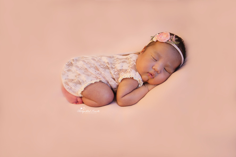 newborn baby girl lying on her tummy in the bum up pose on a pink backdrop