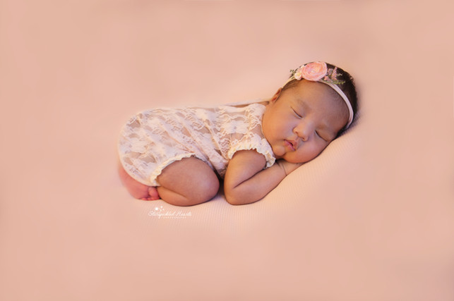 sleeping newborn wearing a lace romper and pink headband laying on her tummy on a pink background for her newborn photoshoot with starspeckled hearts photography