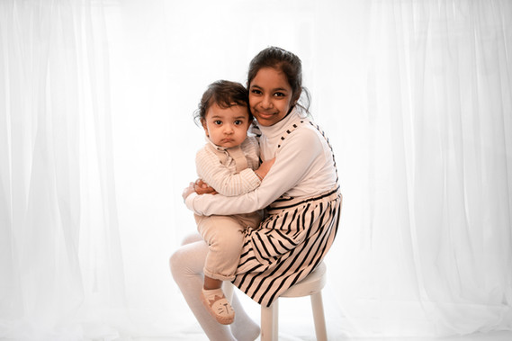 a big sister sitting on a white stool, cradling her one year old little brother, both looking at the camera