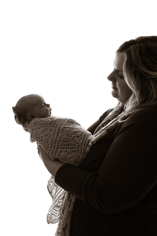 woman holding sleeping newborn profile