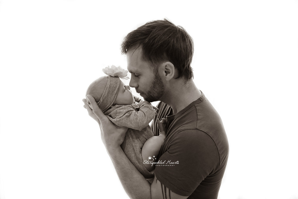 silhouetted shot of man holding newborns nose up to his nose