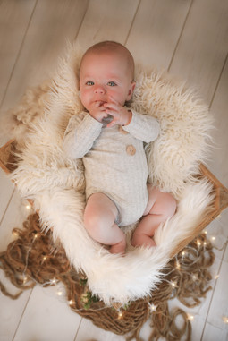 smiling baby boy lying in a wooden crate, wearing a grey romper