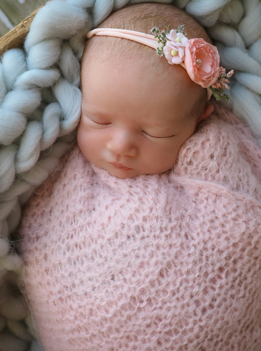 sleeping newborn in pink lying on chunky knitted throw