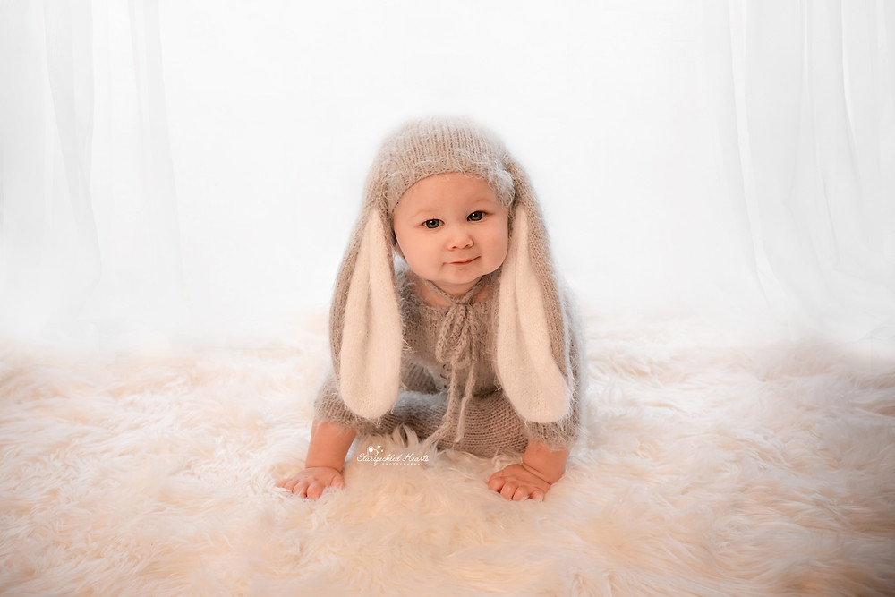 baby boy dressed in a grey knitted rabbit outfit with rabbit ears, sitting on a fluffy rug for his photoshoot with starspeckled hearts photography in hampshire