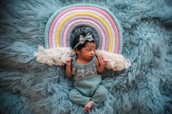 baby girl dressed in blue lying beneath a rainbow