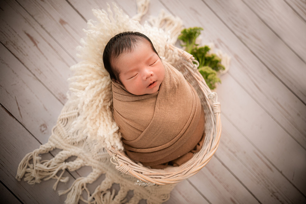 gorgeous sleeping baby boy with a brown swaddle lying in a basket
