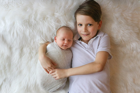 smiling older boy cuddling with his newborn baby brother both wearing all white