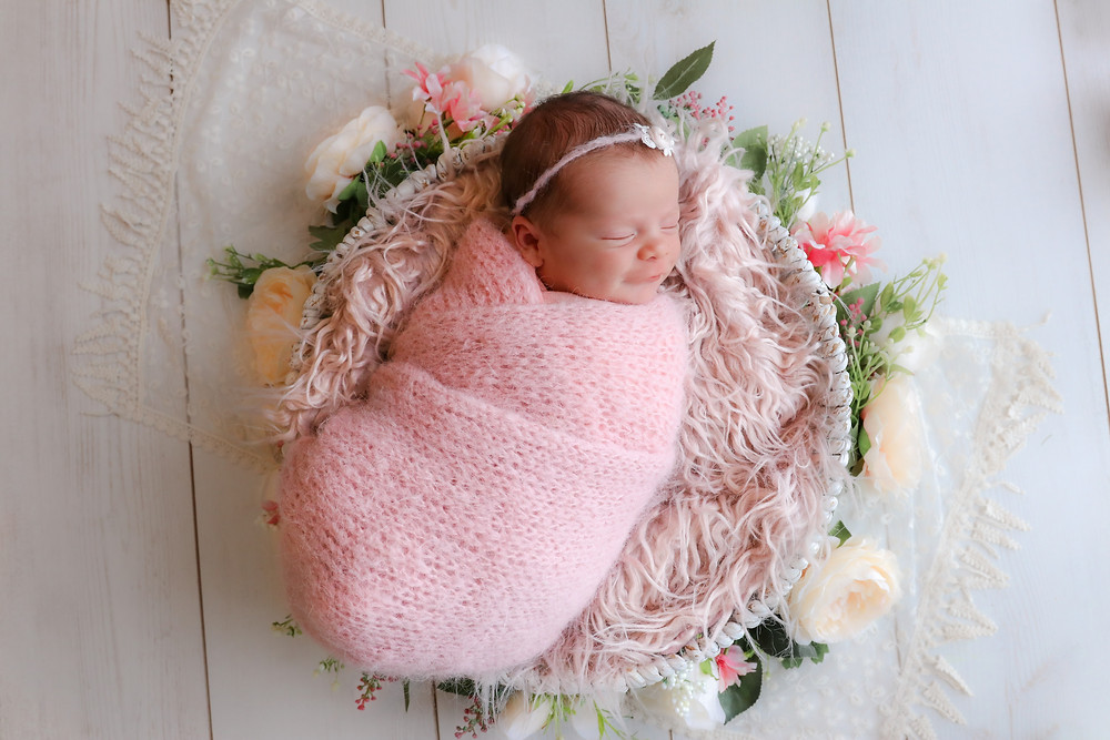 sleeping newborn girl in pink laying in basket surrounded by flowers