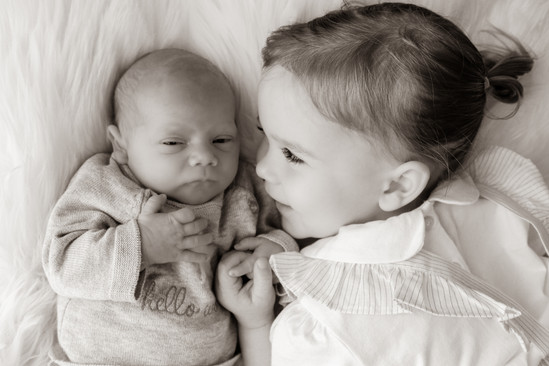 blonde toddler girl lying next to her newborn baby brother holding his hand