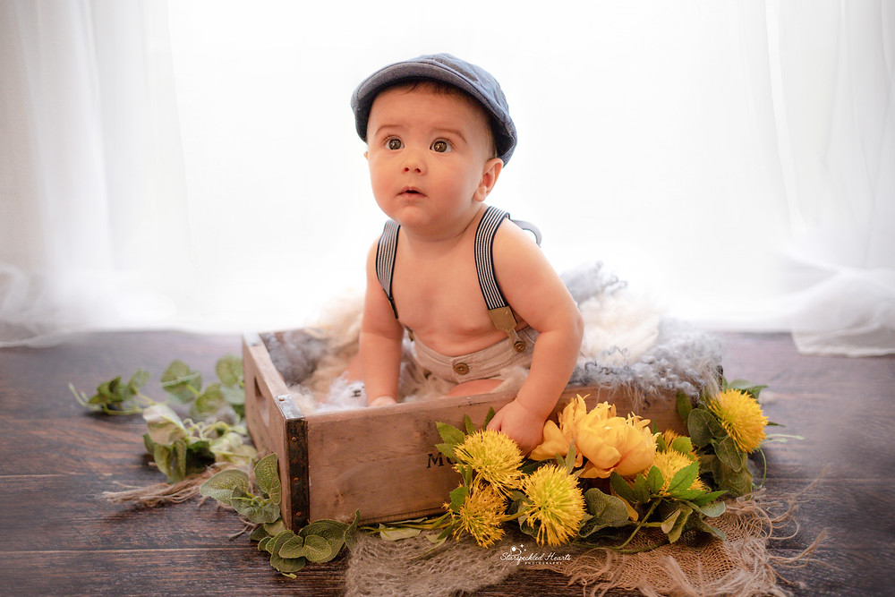 baby boy wearing a flat cap and braces, sitting in a wine crate surrounded by yellow flowers for his little sitter milestone session