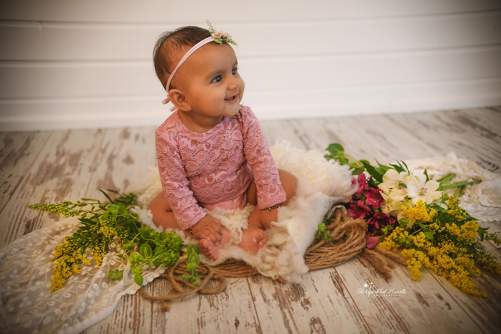 gorgeous smiling baby girl wearing a pink romper suit with a matching headband